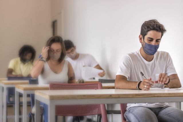 University students in mask doing pre-vestibular test for ENEM